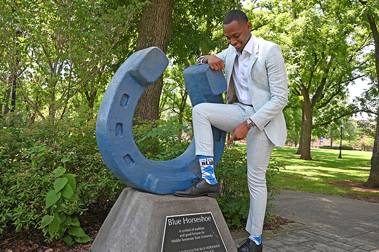"""New MTSU Student Government Association President Winton Cooper shows off his """"I Am True Blue"""" socks at the blue horseshoe in Walnut Grove July 14, 2021, on the Middle Tennessee State University campus in Murfreesboro, Tenn. (MTSU photo by Jimmy Hart)"""