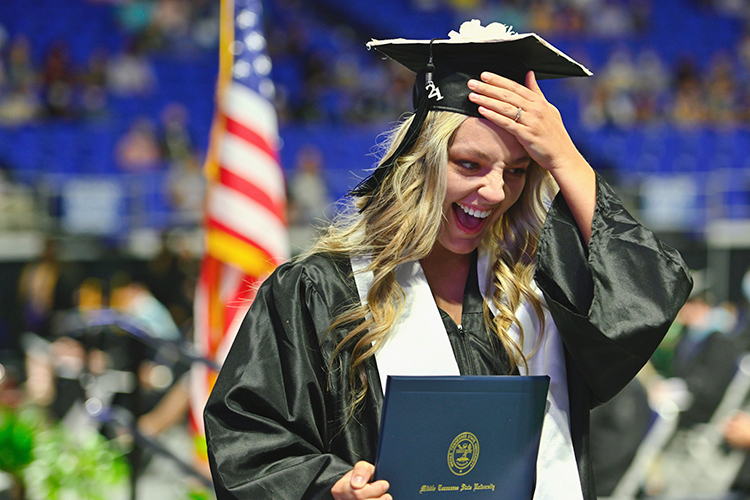 A member of MTSU's first Class of 2021 laughs with pride and a bit of disbelief as she crosses the stage with her degree inside Murphy Center during the second day of the university's spring 2021 three-day weekend of commencement ceremonies in May. Students will return to Murphy Center Saturday, Aug. 7, for the university's summer 2021 commencement ceremony. (MTSU file photo by Cat Curtis Murphy)