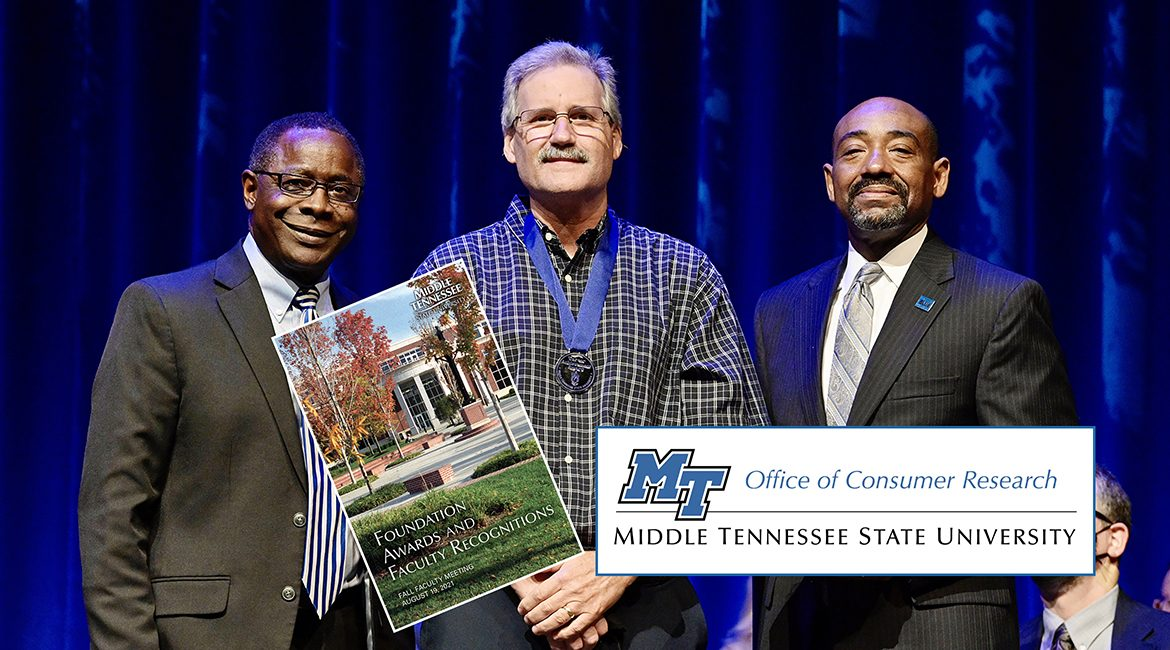 MTSU marketing professor Timothy Graeff, center, proudly wears his new Career Achievement Award medallion Thursday, Aug. 19, after receiving the university's top teaching honor from President Sidney A. McPhee, left, and alumnus Ronald Roberts, vice president of the MTSU Foundation in Tucker Theatre during the 2021 Fall Faculty Meeting. Graeff also is founder of MTSU's Office of Consumer Research. Ten more MTSU professors also were recognized by the MTSU Foundation with awards for their for their accomplishments in and outside the classroom, and McPhee presented his 2021 State of the University address during the gathering. (MTSU photo by Andy Heidt)