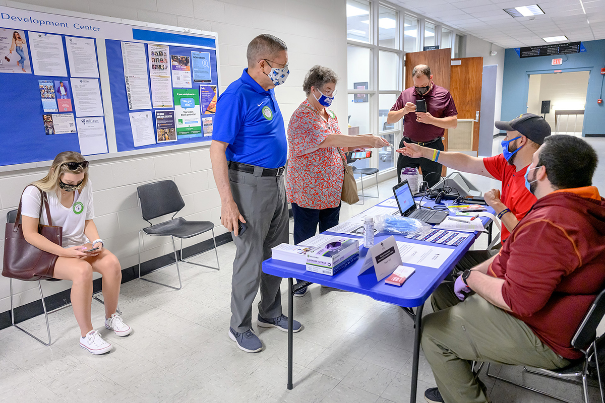 """Prospective donors gather to get and give information to American Red Cross volunteers at MTSU's annual """"Battle of the Branches"""" blood drive Sept. 2 in the Keathley University Center. At center, alumni Ricky and Margaret Smith share their appointment time and other check-in details with donor ambassador Shawn Tengowski as donor ambassador Michael Braitwaite looks on. Alumna Carrie Altizer, seated at left, checks information on her phone before her donation while Rick Chapman, standing at center right, director of MTSU's Student Health Services, looks at his own phone. Donors from across the campus and surrounding community gave 80 pints of blood to help as many as 225 people across the region and state. (MTSU photo by J. Intintoli)"""