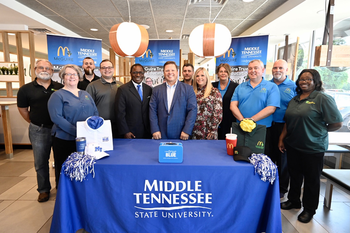 McGuire Management Group employees attend the Wednesday, Aug. 4, announcement of a new educational partnership with MTSU, allowing them to attend MTSU tuition-free starting this fall if they meet qualifying criteria. The partnership signing by MTSU President Sidney A. McPhee, center left, and McGuire owner/operator Jonathon McGuire, center right, occurred at the McDonald's restaurant on Memorial Boulevard. It is one of 20 owned in the Nashville area by Jonathon McGuire. (MTSU photo by J. Intintoli)