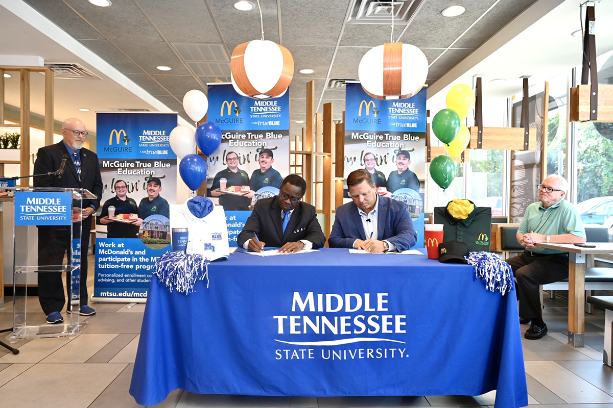 MTSU President Sidney A. McPhee, left, and McGuire Management Group owner/operator Jonathon McGuire sign the memorandum of understanding agreement formalizing the McGuire True Blue Education Partnership Wednesday, Aug. 4, at the McDonald's franchise at 1706 Memorial Blvd., in Murfreesboro. The agreement calls for McGuire employees to attend MTSU tuition-free if they meet qualifying criteria. (MTSU photo by J. Intintoli)