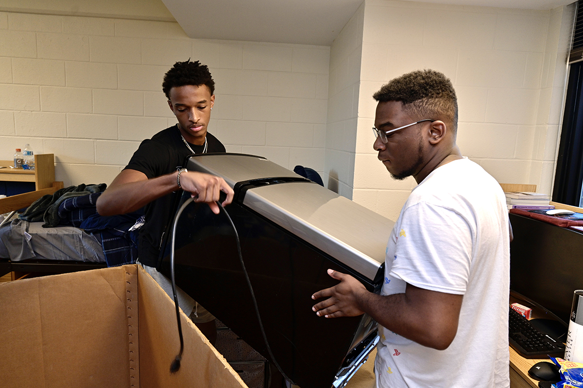 Friends and now college roommates Justin Tatum, left, of Cane Ridge, Tenn., and Elijah Robinson of Nashville, Tenn., lift a mini refrigerator out of a large box for their Corlew Hall dorm room. The freshmen are awaiting the start of fall semester classes Monday, Aug. 23. (MTSU photo by Andy Heidt)