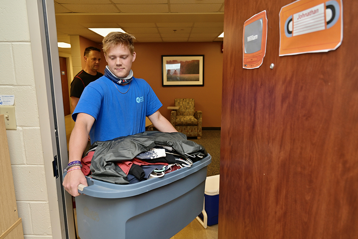 Will Voyles, 18, of Murfreesboro, Tenn., brings in a load of personal items and clothes Wednesday, Aug. 18, as he moves in to his Corlew Hall dorm. Voyles, a Rockvale High School May 2021 graduate, will be studying exercise science. His father, Shane Voyles, waits to enter the room. Students have scheduled move-in times through Saturday, Aug. 21. (MTSU photo by Andy Heidt)