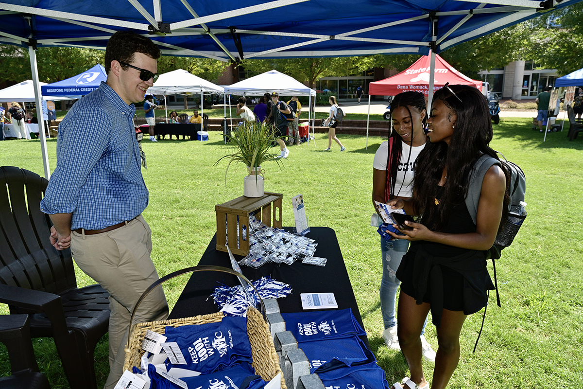 Murfreesboro Medical Clinic marketing specialist Dalton Tracy, left, provides information about the health care facility to MTSU students Ty Miles, center, of Murfreesboro, and Eve Hoffman of Liberia, Africa, during the first day of the two-day MTSU New Student and Family Programs Meet Murfreesboro event Tuesday, Aug. 24, in the Student Union Commons. Miles is a senior graphic design major while Hoffman is a junior fashion merchandising major. (MTSU photo by Andy Heidt)