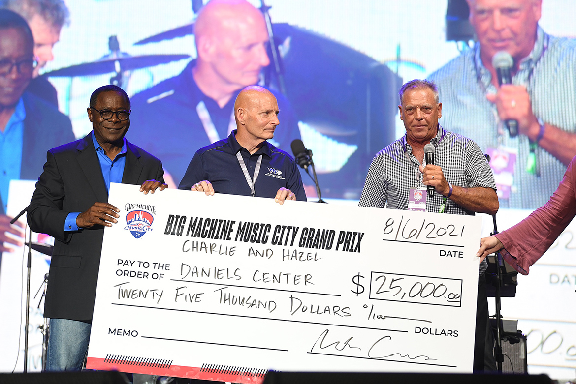 From left, MTSU President Sidney A. McPhee and retired Army Lt. Gen. Keith Huber, MTSU's senior advisor for veterans and leadership initiatives, accept a $25,000 donation from a representative of the Big Machine Music City Grand Prix at the Freedom Friday concert held Friday, Aug. 6, 2021, as part of the inaugural IndyCar race in Nashville, Tenn. The donation will support the university's Charlie and Hazel Daniels Veterans and Military Family Center. (MTSU photo by James Cessna)