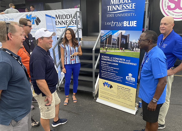 From right, Kelly Strong, director of the MTSU School of Concrete and Construction Management; MTSU President Sidney A. McPhee; and former professor Heather Brown brief officials from industry partner Somero Enterprises Friday, Aug. 6, 2021, at MTSU's hospitality area on the grounds the Big Machine Music City Grand Prix in Nashville, Tenn., about the new $40 million facility for the concrete program currently under construction on the Murfreesboro, Tenn., campus. (MTSU photo by Andrew Oppmann)