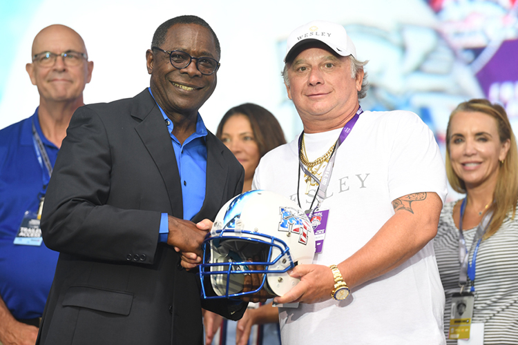 MTSU President Sidney A. McPhee, front left, presents a special military-themed football helmet to former MTSU student Chuck McDowell at the Freedom Friday concert held Friday, Aug. 6, 2021, as part of the inaugural Big Machine Music City Grand Prix in Nashville, Tenn. McDowell, CEO of concert sponsor Wesley Financial Group, was recognized for his support of the university's Charlie and Hazel Daniels Veterans and Military Family Center. Also pictured in the background, from left, are Kelly Strong and Heather Brown, director and former professor, respectively, from the MTSU School of Concrete and Construction Management; and Hilary MIller, director of the Daniels Center. (MTSU photo by James Cessna)