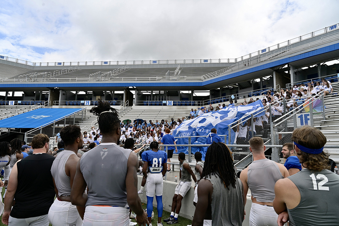 As Blue Raider football players look on, a group of MTSU students unfurl the giant Blue Zoo banner for the first time in two years on Thursday, Aug. 19, inside Floyd Stadium in preparation for the upcoming football season. (MTSU photo by Andy Heidt)