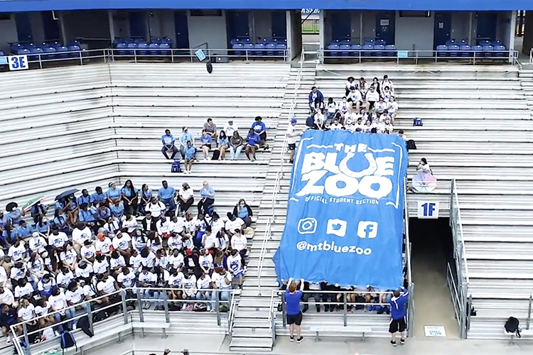 A group of MTSU students unfurl the giant Blue Zoo banner for the first time in two years on Thursday, Aug. 19, inside Floyd Stadium in preparation for the upcoming football season. (MTSU screen capture)