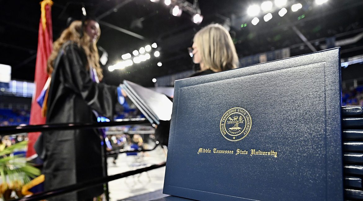 A stack of MTSU diploma covers awaits graduates as they cross the stage inside Murphy Center during the second day of the university's spring 2021 three-day weekend of commencement ceremonies in May in this file photo. Students will return to Murphy Center Saturday, Aug. 7, for the university's summer 2021 commencement ceremony. (MTSU file photo by J. Intintoli)