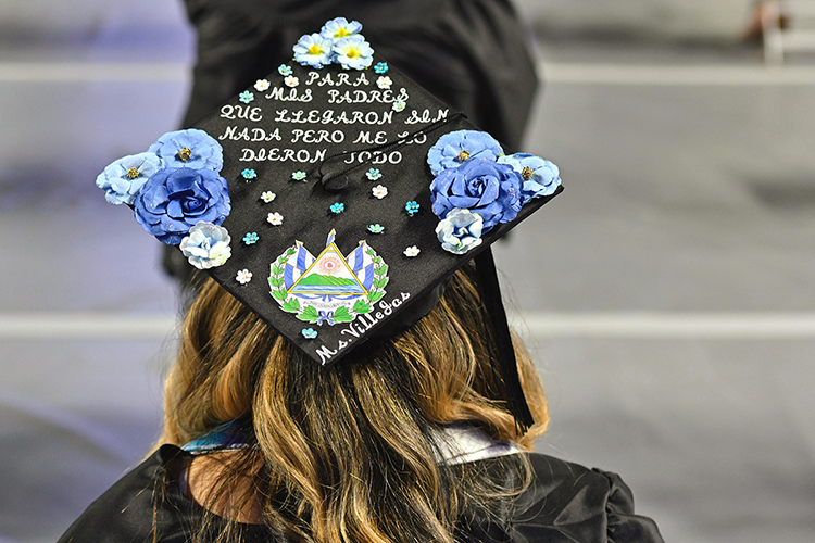 """New MTSU College of Education graduate Andrea Villegas proudly wears her customized mortarboard during the university's spring 2021 three-day weekend of commencement ceremonies in May. Villegas, who now teaches at Stewartsboro Elementary School, wrote """"For my parents, who came with nothing but gave me everything"""" on her graduation cap. MTSU students will return to Murphy Center Saturday, Aug. 7, for the university's summer 2021 commencement ceremony. (MTSU file photo by Cat Curtis Murphy)"""