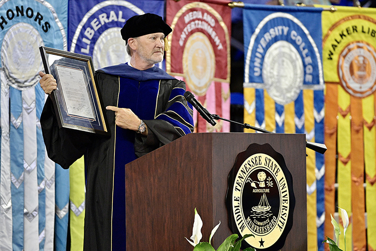 """MTSU human sciences professor Rick Cottle, 2020-21 president of the university's Faculty Senate, holds his framed rejection letter from Auburn University, where he later earned undergraduate and doctoral degrees, while encouraging students to """"show up and do the work"""" at MTSU's summer 2021 commencement ceremony Saturday, Aug. 7, in Murphy Center. MTSU presented degrees to 825 new graduates of the August Class of 2021 at the event. (MTSU photo by Andy Heidt)"""