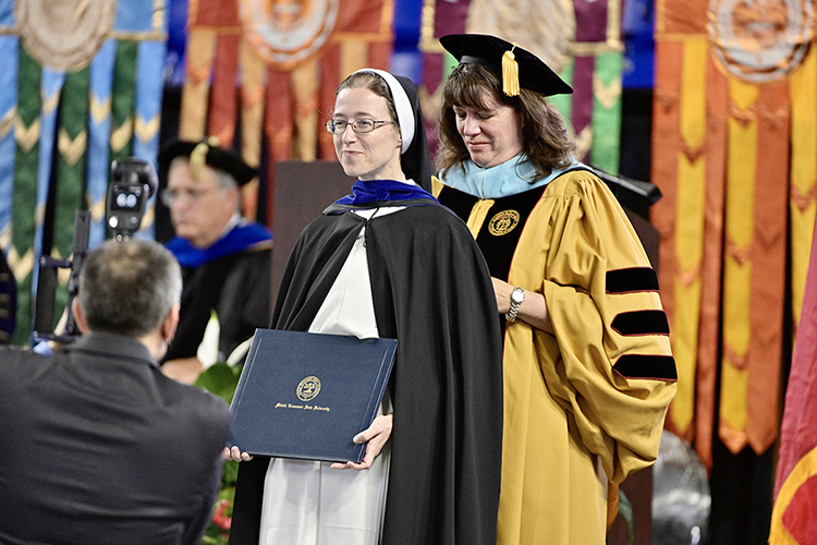 Sister Cecelia Ann Wanner, left, president of Aquinas College in Nashville, smiles gently as MTSU mathematical sciences professor Alyson Lischka carefully adjusts the academic hood around Wanner's neck and shoulders to signify completion of her doctoral degree in math and science education at MTSU's summer 2021 commencement ceremony Saturday, Aug. 7, in Murphy Center. MTSU presented degrees to 825 new graduates of the August Class of 2021 at the event. (MTSU photo by Andy Heidt)