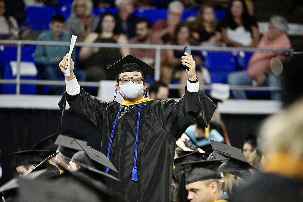 A new MTSU master's graduate happily celebrates his accomplishment and acknowledges supporters in the Murphy Center audience during the university's summer 2021 commencement ceremony Saturday, Aug. 7. MTSU presented degrees to 825 new graduates of the August Class of 2021 at the event. (MTSU photo by Andy Heidt)