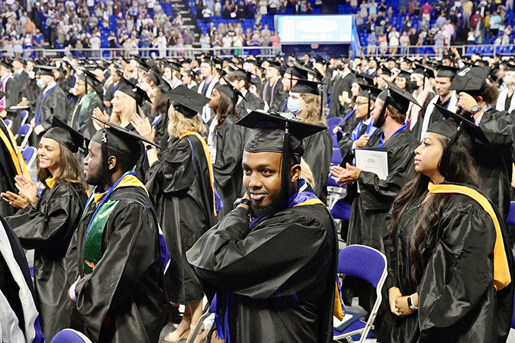 """Members of MTSU's August Class of 2021 applaud their success after they """"turn the tassels"""" on their mortarboards to signify their graduation during the university's summer 2021 commencement ceremony Saturday, Aug. 7, in Murphy Center. MTSU presented degrees to 825 new graduates of the August Class of 2021 at the event. (MTSU photo by Andy Heidt)"""