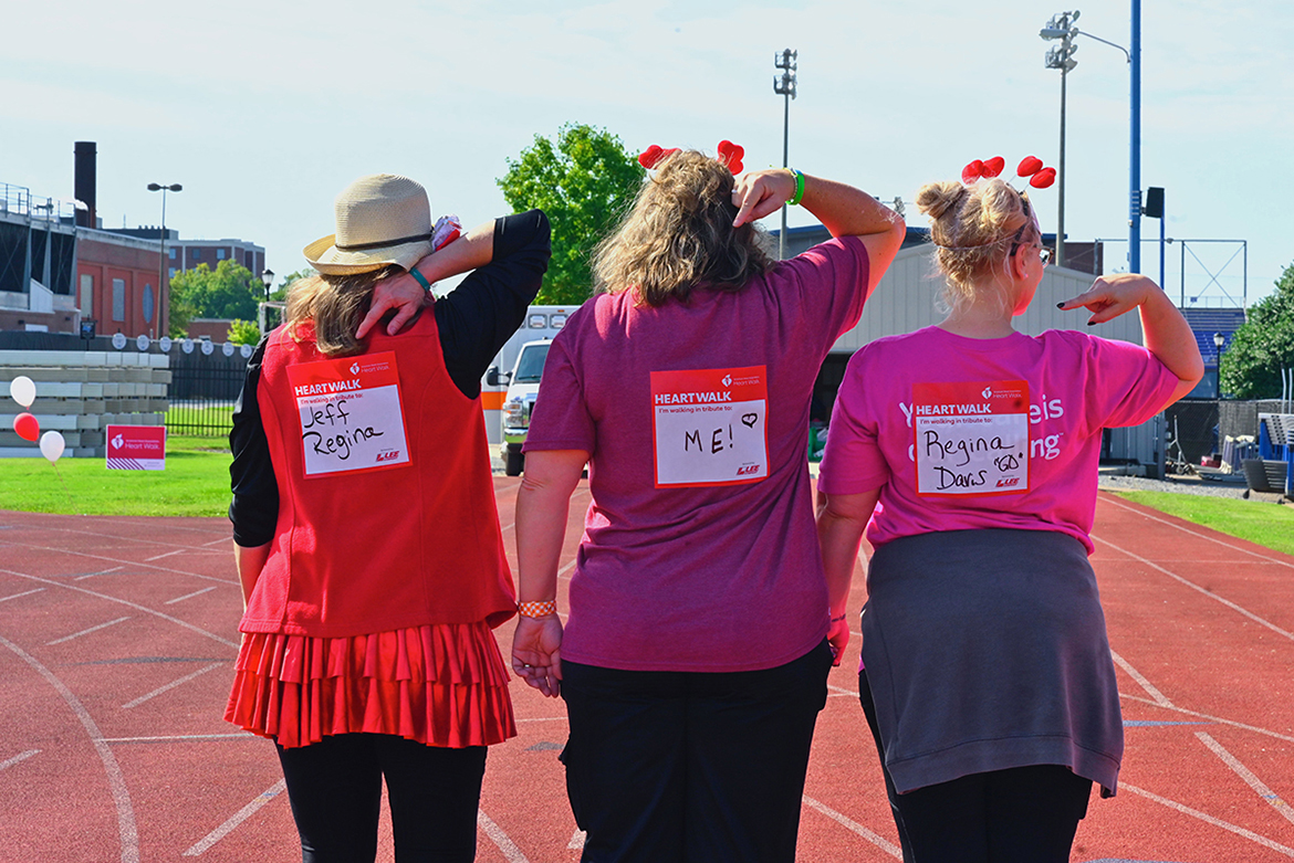 Three Rutherford County Heart Walk participants indicate the individuals for whom they are walking Sept. 25 at Dean A. Hayes Track and Soccer Stadium. (MTSU photo by Cat Curtis Murphy)