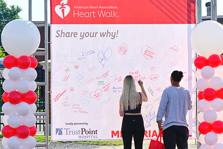 Participants in the 2021 Rutherford County Heart Walk write their reasons for walking to raise funding for heart disease research on a white board Sept. 25 at Dean A. Hayes Track and Soccer Stadium. (MTSU photo by Cat Curtis Murphy)