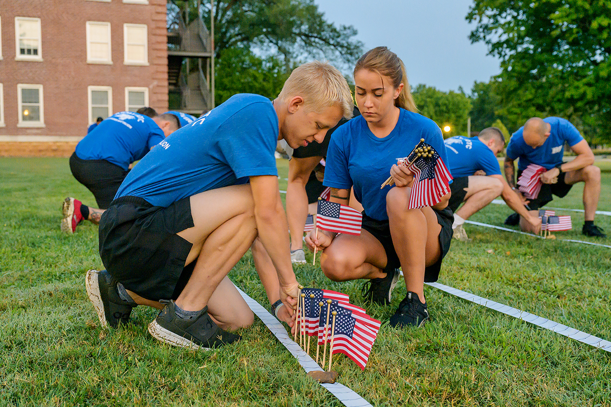MTSU ROTC cadets Ethan Hawks and Aiyanna Gallant plant U.S. flags in a grassy area outside the Veterans Memorial and Tom H. Jackson Building at 6 a.m. Friday, Sept. 10, to help commemorate the 20th anniversary of 9/11. Sixty cadets, student veterans, SGA members and military science faculty took part at this location and in Floyd Stadium. Nearly 3,000 flags and 2,977 names of victims who died in the Sept. 11, 2001, attack on U.S. soil during a series of four coordinated terrorist suicide attacks by the extremist group al-Qaida on U.S. landmarks. (MTSU photo by Andy Heidt)