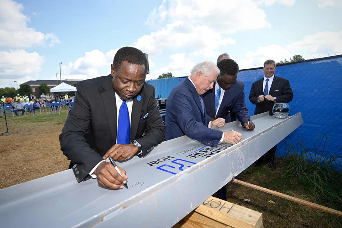 MTSU President Sidney A. McPhee, left, and MTSU Board of Trustees members J.B. Baker, left, Darrell Freeman, Steve Smith and Pete Delay sign the ceremonial final beam to be placed at the top of the School of Concrete and Construction Management building Tuesday, Sept. 14, in the Bragg Parking lot adjacent to the construction site. (MTSU photo by J. Intintoli)