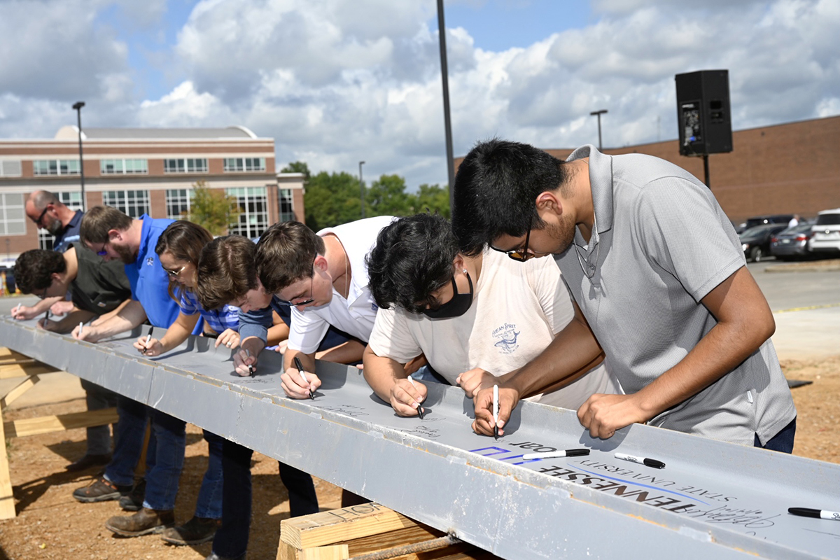 MTSU students sign the ceremonial final beam to be placed at the top of the School of Concrete and Construction Management building Tuesday, Sept. 14, near the Bragg Parking lot adjacent to the construction site. The 54,000-square-foot building is expected to be completed in 15 months, in time for Fall 2022 classes. The facility features classrooms, faculty and staff offices and laboratory space for Concrete Industry Management and Construction Management, both of which provide interns and ready-to-work graduates awaiting potentially lucrative careers. (MTSU photo by J. Intintoli)