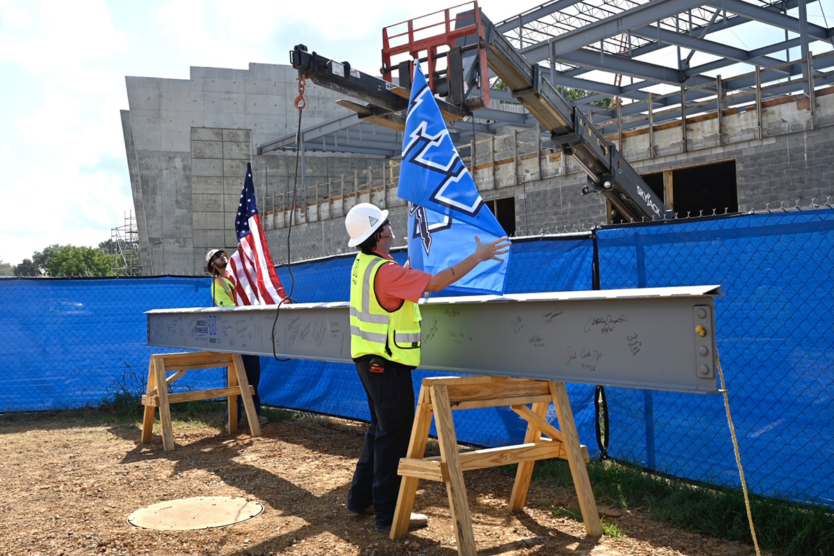 Project superintendents Wyatt Keeton, left, and Tom Hudson with Hoar Construction prepare the U.S. and MTSU flags placed on the final beam to be placed on top of the MTSU School of Concrete and Construction building Tuesday, Sept. 14. Campus officials celebrated with a topping-out ceremony near the construction site. (MTSU photo by J. Intintoli)