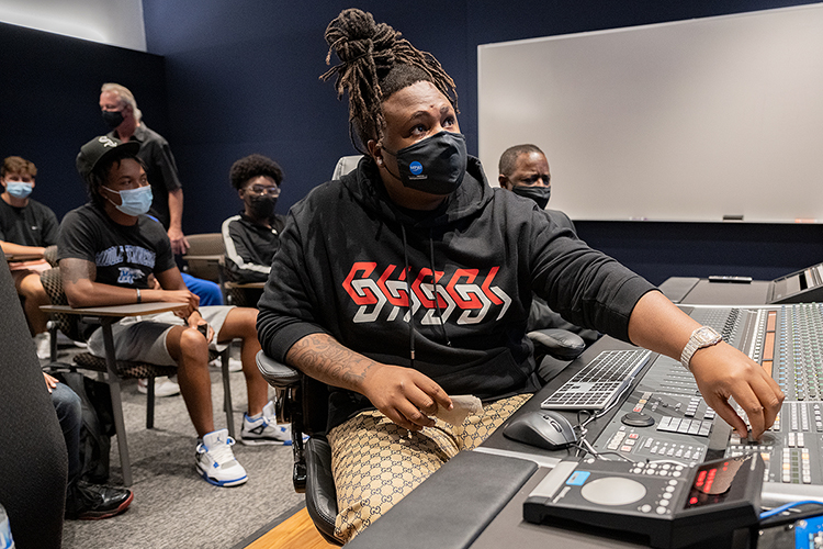 """Memphis native and Grammy-nominated hip-hop producer BryTavious """"Tay Keith"""" Chambers, 25, turns up the volume to one of his produced tracks Wednesday, Sept. 29, on the campus of his alma mater, Middle Tennessee State University, during a special """"sneak-peek"""" visit to the MTSU Department of Recording Industry's new studios on campus. Listening behind him are a group of MTSU students and university president Sidney A. McPhee. (MTSU photo by Cat Curtis Murphy)"""