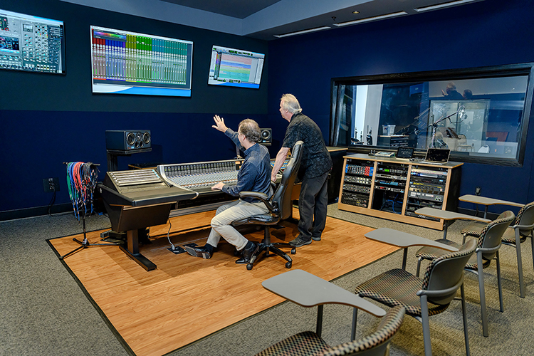 John Merchant, seated, chair of the Department of Recording Industry at Middle Tennessee State University, points out an option on the wall display screen to professor Dan Pfeifer in Studio D, one of the department's two newly relocated, customized, expandable recording facilities for students in the East Main Building on campus. Pfeifer is the co-chair of a committee overseeing the nearly $2 million project, which covers almost 5,000 square feet of recording space, control rooms, equipment rooms and an open gathering/reception area. (MTSU photo by J. Intintoli)