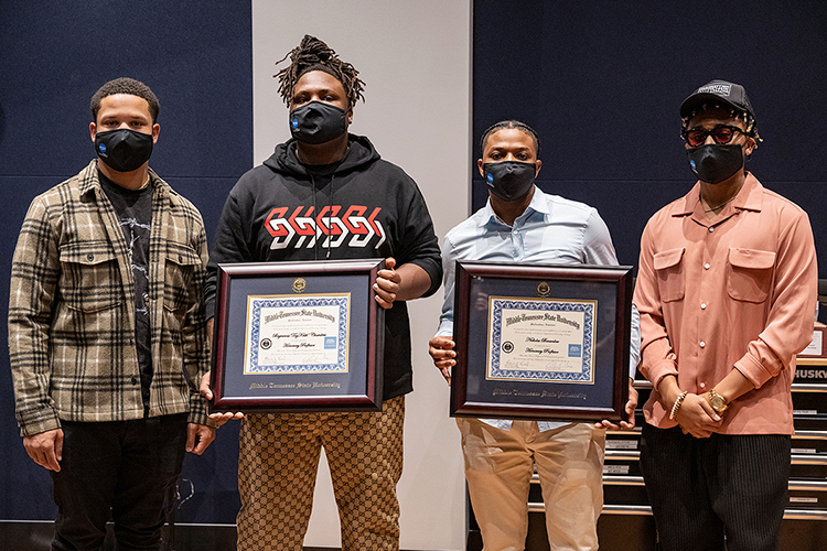 """Memphis native and Grammy-nominated hip-hop producer BryTavious """"Tay Keith"""" Chambers, second from left, holds the honorary professorship certificate he received from Middle Tennessee State University Wednesday, Sept. 29, during a special """"sneak-peek"""" visit to his alma mater for a tour of the MTSU Department of Recording Industry's new studios on campus. Pictured from left are Chambers' manager, former MTSU student and Howard University grad Cambrian Strong; Chambers; MTSU alumnus Nick Brownlow, Chambers' PR director and executive at their Drumatized record label and production company, who was also honored; and fellow MTSU alumnus Tyland Jackson, Chambers' stylist. (MTSU photo by Cat Curtis Murphy)"""