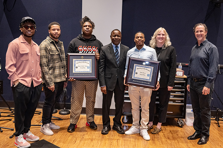 """Memphis native and Grammy-nominated hip-hop producer BryTavious """"Tay Keith"""" Chambers, third from left, holds the honorary professorship certificate he received from Middle Tennessee State University Wednesday, Sept. 29, during a special """"sneak-peek"""" visit to his alma mater for a tour of the MTSU Department of Recording Industry's new studios on campus. Pictured from left are fellow MTSU alumnus Tyland Jackson, Chambers' stylist; Chambers' manager, former MTSU student and Howard University grad Cambrian Strong; Chambers; MTSU President Sidney A. McPhee; MTSU alumnus Nick Brownlow, Chambers' PR director and executive at their Drumatized record label and production company, who was also honored; College of Media and Entertainment Dean Beverly Keel; and John Merchant, chair of the Department of Recording Industry. (MTSU photo by Cat Curtis Murphy)"""