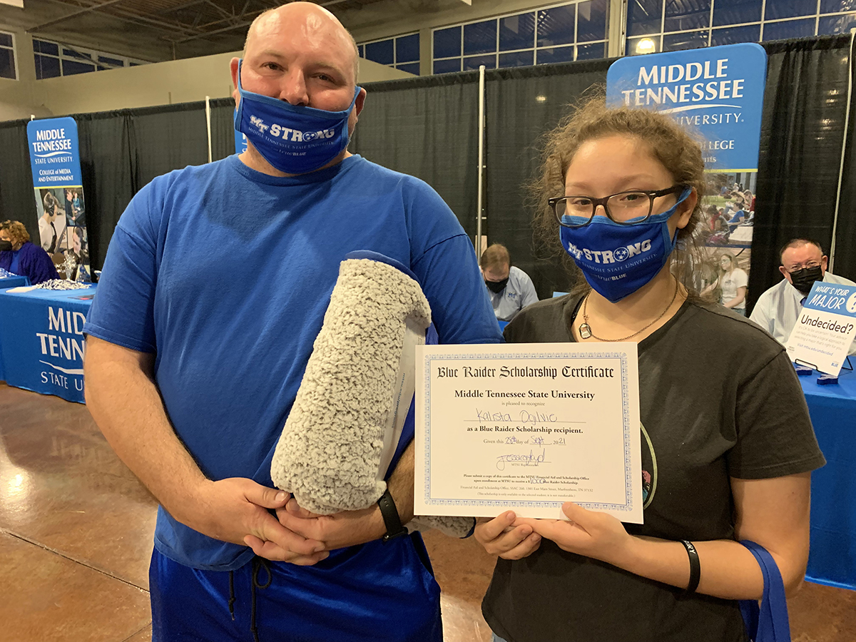 Kalista Ogilvie, right, of Clarksville, Tenn., received a $1,500 scholarship from MTSU President Sidney A. McPhee and her stepfather, Andrew Sims, won an MTSU blanket by attending the university's True Blue Tour event Tuesday, Sept. 28, at the Wilma Rudolph Event Center. Ogilvie is highly interested in MTSU's horse science, theater and arts programs. (MTSU photo by Randy Weiler)