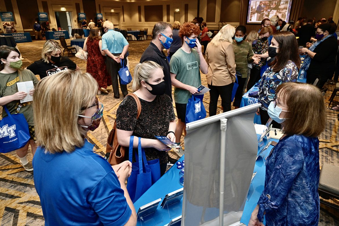 Courtney Lent, center, visits with one of MTSU's academic colleges during the university's True Blue Tour event recently at the Franklin Marriott Cool Springs. Lent, 32, will be returning as a student along with her stepson, Nathan Lent, 17, who will be a freshman in fall 2022, with plans to major in photography and minor in graphic design in the College of Liberal Arts. Courtney Lent plans to study psychology. She started at MTSU in 2007, but dropped out to enter the workforce. (MTSU photo by Andy Heidt)