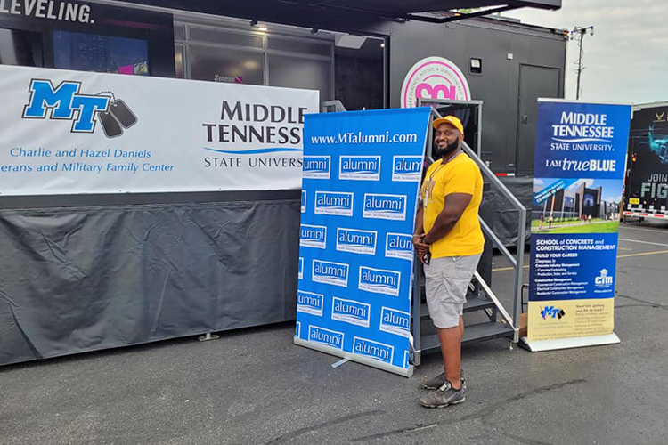 Middle Tennessee State University alumnus and former Blue Raider football player Germayle Franklin poses next to the MTSU hospitality area in August during the Big Machine Music City Grand Prix in Nashville, Tenn. Franklin operates Franklin's Fruit Tea in Murfreesboro. He created his special tea while an undergraduate and now offers it on campus through Dwight's Mini Mart in Keathley University Center. (Submitted photo)