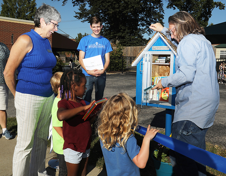 Children from the Ann Campbell Early Learning Center on North Baird Lane examine books at the Sept. 27 ribbon-cutting ceremony for the first Little Free Library sponsored by Omicron Delta Kappa and Phi Kappa Phi honor societies. Pictured, from left, are Connie Casha, director of early learning programs for the MTSU College of Education; Liam McBane, ODK chapter president; and Nathan Wahl, PKP student vice president. (MTSU photo by Marsha Powers).