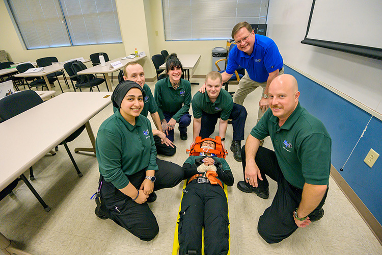 Middle Tennessee State University Advanced EMT instructor Randy White, top right, is shown with EMT students, from left, Morsell Durani, Chandler Mangrum, Makenna Stark, Cale Brown, Andrew Hill, and Claudia Tepox (on stretcher) inside a classroom at the Miller Education Center on Bell Street. (MTSU photo by Andy Heidt)