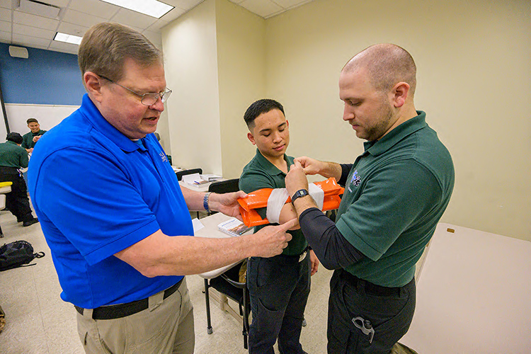 """Middle Tennessee State University Advanced EMT instructor Randy White, left, guides student Ryan Painter, right, and """"victim"""" and fellow student Devin Southivong during class in the Miller Education Center on Bell Street. (MTSU photo by Andy Heidt)"""