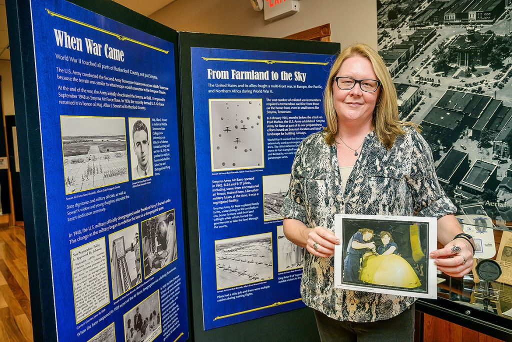 """Kira Duke, education specialist at Middle Tennessee State University's Center for Historic Preservation, holds a Library of Congress digital collection photo of Tennessee women working on a WWII """"Vengeance"""" dive bomber, at the Heritage Center of Murfreesboro and Rutherford County in Murfreesboro, Tenn., on Oct. 13, 2021. MTSU's center recently landed a $43,000 Library of Congress grant for a research project centered around the impact of WWII on Tennesseans. (MTSU photo by Andy Heidt)"""